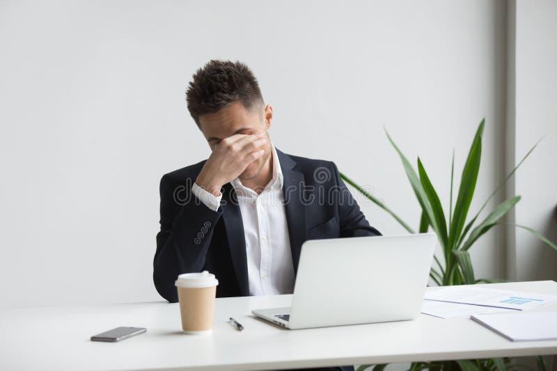 Frustrerad stressad affärsmankänsla som tröttas av bärbara datorn, ögonfa royaltyfria foton