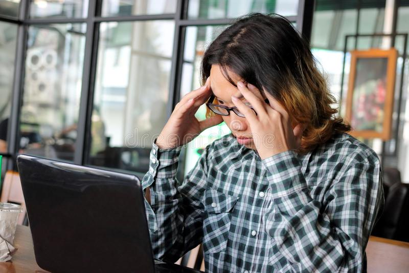 Frustrerad stressad ung asiatisk affärsman med händer på head känsla som i regeringsställning tröttas eller svikas mot hans arbet royaltyfria foton