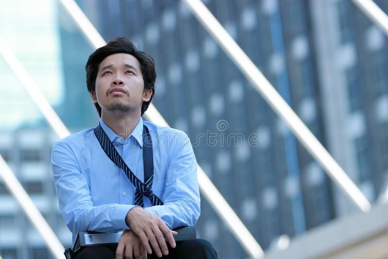 Frustrerad stressad ung asiatisk affärsmankänsla som evakueras, och huvudvärk mot jobb på stads- byggnad med kopieringsutrymmebac royaltyfria foton