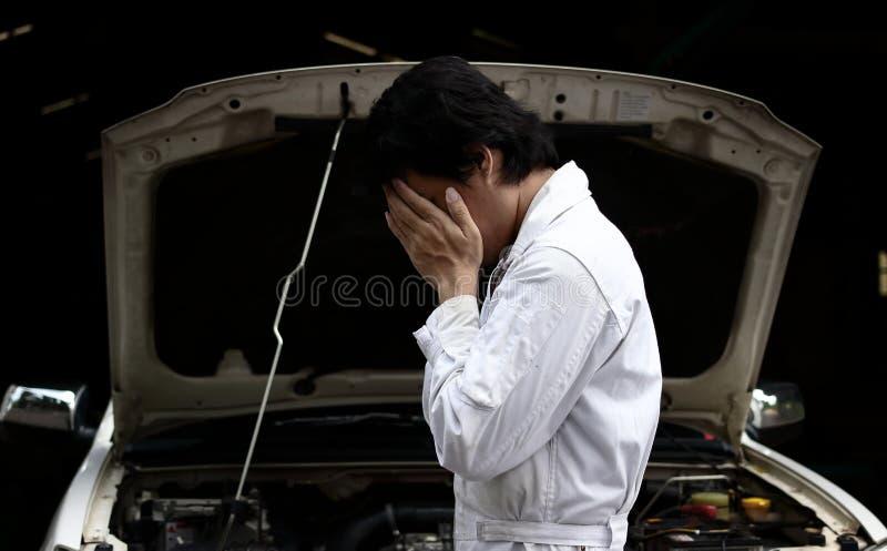 Frustrerad stressad ung mekanikerman i den vita enhetliga beläggningframsidan med händer med bilen i öppen huv på garaget Auto re royaltyfri fotografi