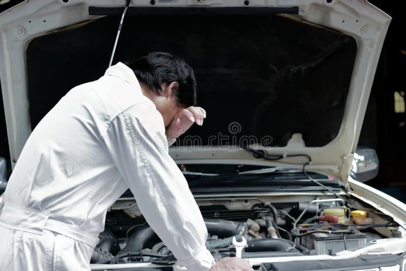 Frustrerad stressad ung mekanikerman i vit enhetlig känsla som tröttas med bilen i öppen huv på reparationsgaraget arkivfoton
