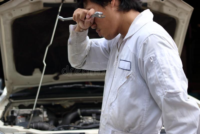 Frustrerad stressad ung mekanikerman i vit enhetlig känsla som tröttas mot bilen i öppen huv på reparationsgaraget royaltyfri foto