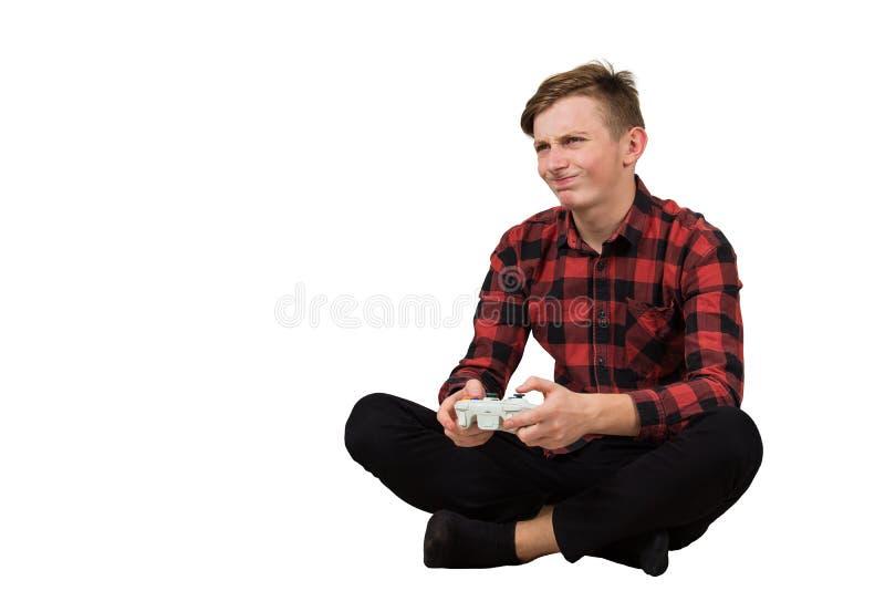 Frustrerad tonåring som spelar videospel isolerade över vit bakgrund Uppspänd tonåring på golvet med en royaltyfria foton
