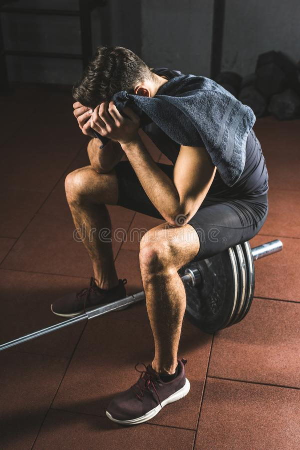 Frustrerad ung idrottsman med handduken i handsammanträde på skivstång arkivfoto
