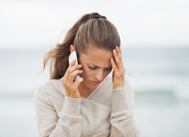 Frustrerad ung kvinna i tröja på den talande mobiltelefonen för strand royaltyfri foto