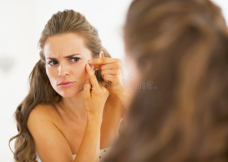 Frustrerad ung kvinna som pressar akne royaltyfria foton