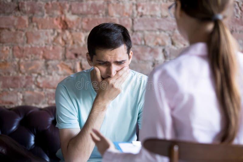 Frustrerad ung man på ett mottagande med psykologen royaltyfria foton