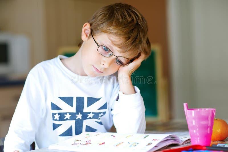 Frustrerad ungepojke med hemmastadd danandeläxa för exponeringsglas arkivbilder