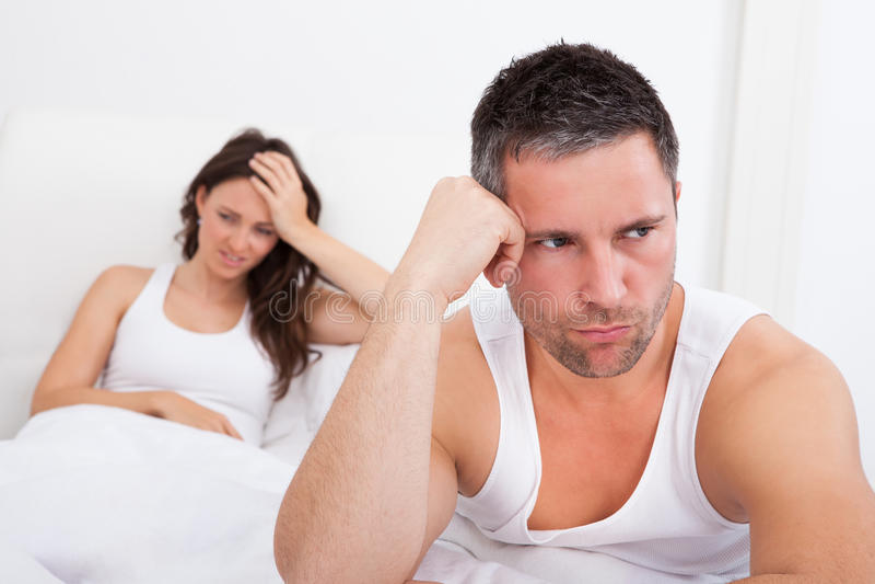 Frustrerade par på säng arkivbild