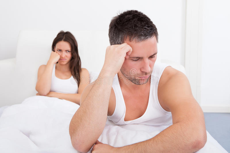 Frustrerade par på säng royaltyfri foto