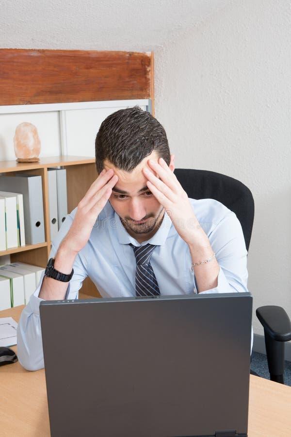 Frustrerat affärsmansammanträde på skrivbordet med handen på huvudet i regeringsställning arkivfoton