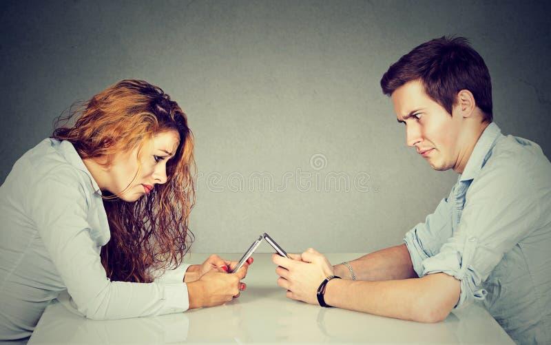 Frustrerat förargat ung kvinna- och mansammanträde på tabellen med smartphonen royaltyfri fotografi
