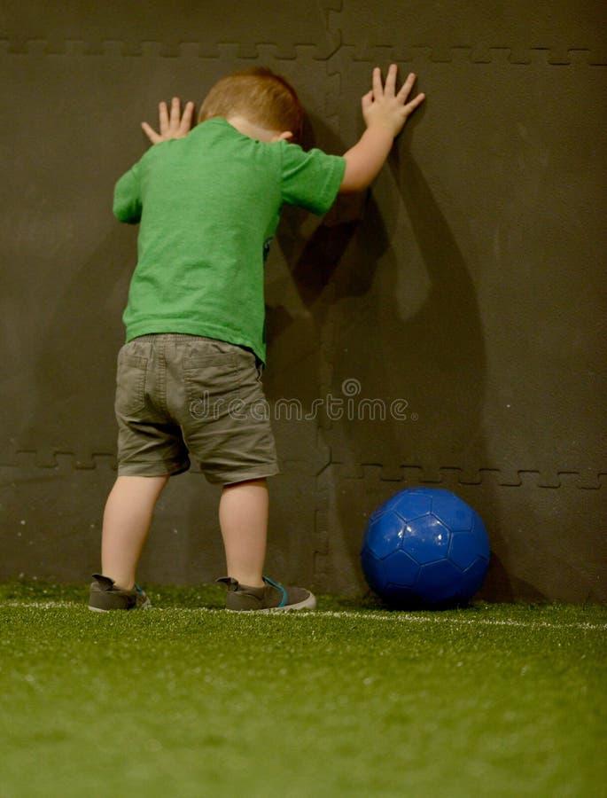 Frustrerat litet barn som spelar fotboll royaltyfri bild