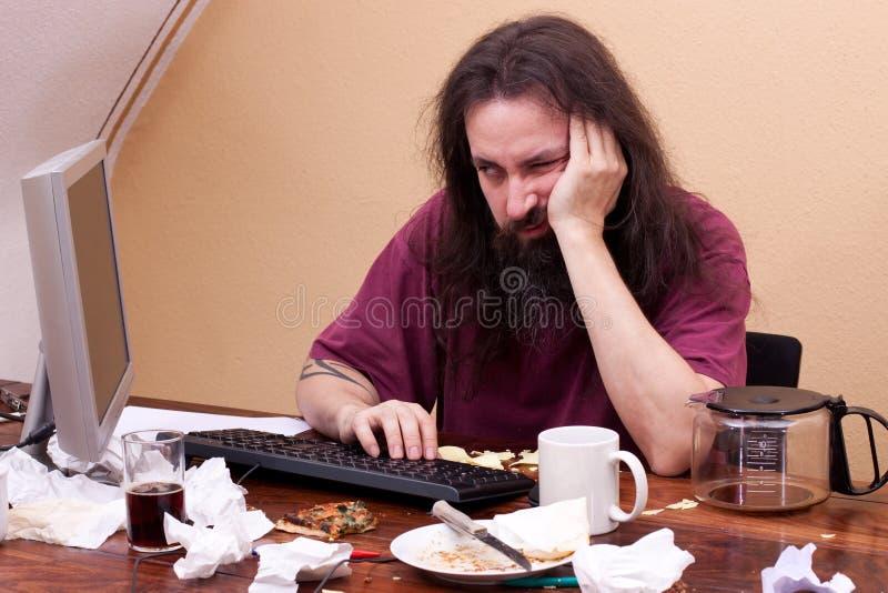 Frustrerat mansammanträde på datoren och är tänkande royaltyfri foto