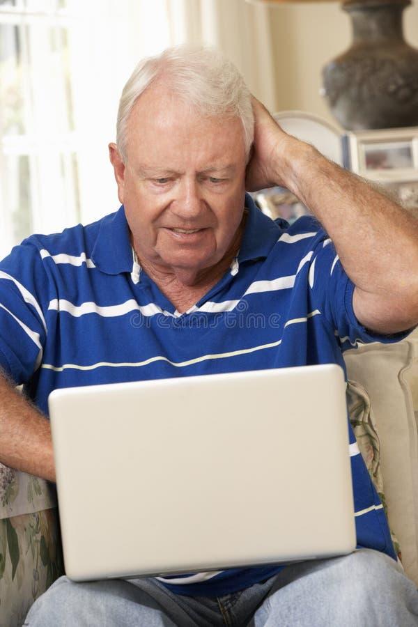 Frustrerat pensionerat sammanträde för hög man på Sofa At Home Using Laptop arkivbilder