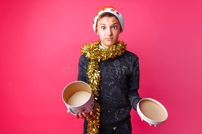 Frustrerat tonårigt i jultomtenhatt och med glitter på hennes hals, med f arkivbilder