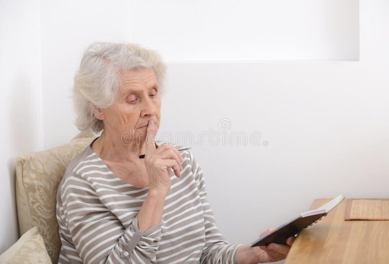 Frustrierte ältere Frau, die am Tisch mit Notizbuch sitzt stockbilder