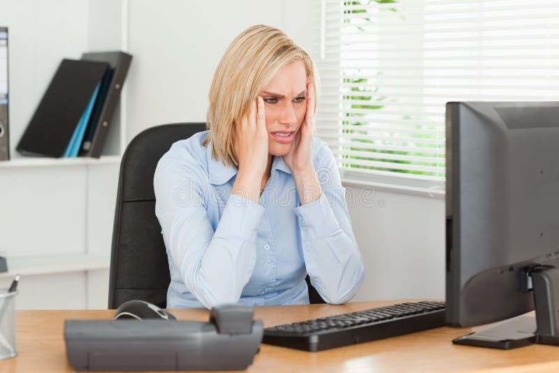 Frustrierte berufstätige Frau vor einem Bildschirm lizenzfreie stockfotos