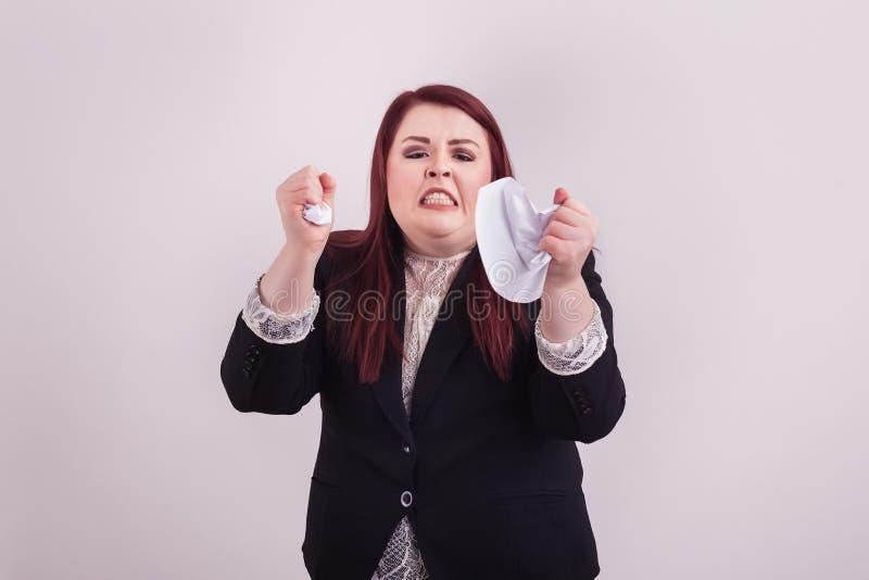 Frustrierte betonte junge Berufsfrau, die herauf Papier mit ihren Händen zerbröckelt lizenzfreies stockbild