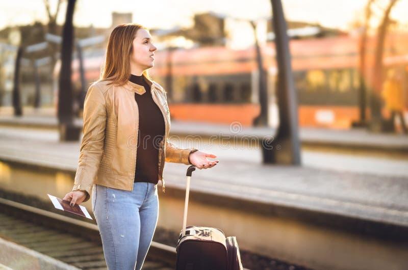 Frustrierte Frau an der Bahnstation Spät verzögert, annulliert stockfotos