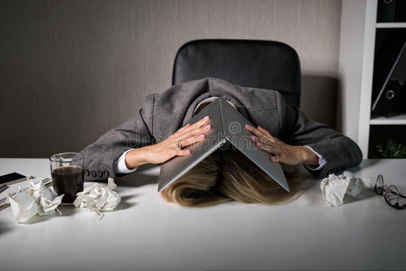 Frustrierte Frau, die unter Laptop im Büro sich versteckt stockfoto