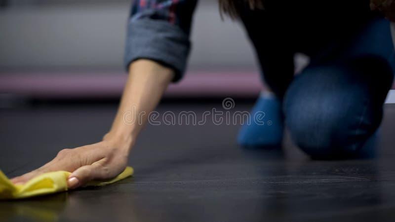 Frustrierte Frau versucht, einen Fleck auf dem Boden mit Reinigungsprodukt zu entfernen lizenzfreie stockbilder