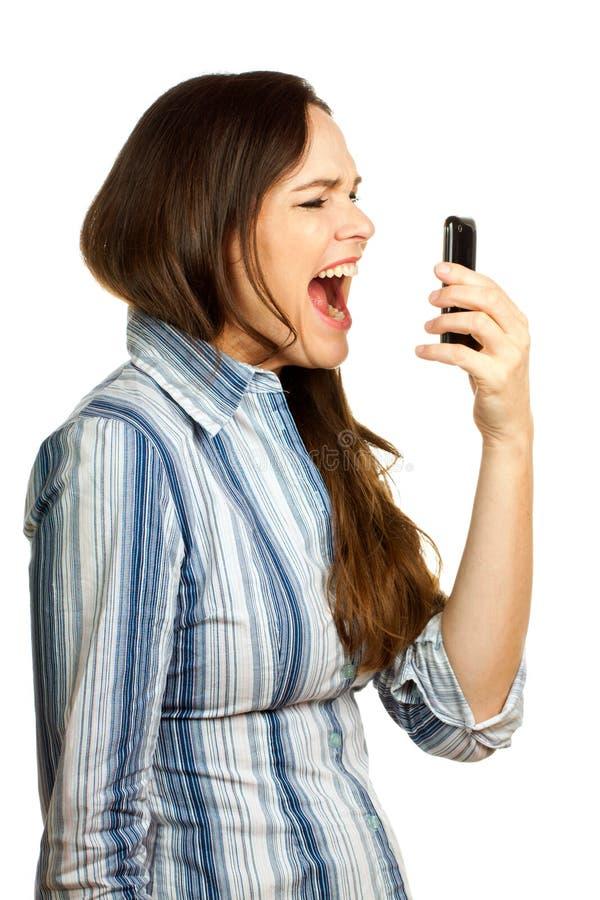 Frustrierte Geschäftsfrau, die an ihrem Telefon kreischt stockfotografie