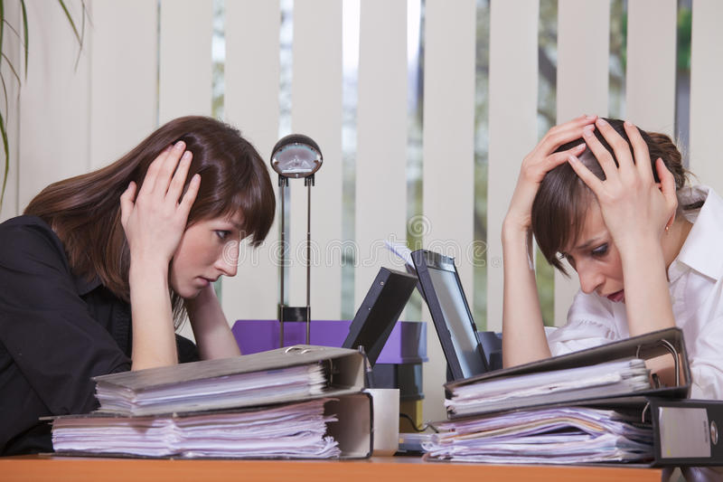Frustrierte Geschäftsfrauen durch Arbeit lizenzfreies stockbild