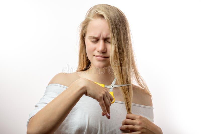 Frustrierte junge Blondine, habend Probleme mit dem schlechten Haar auf weißem Hintergrund stockfoto