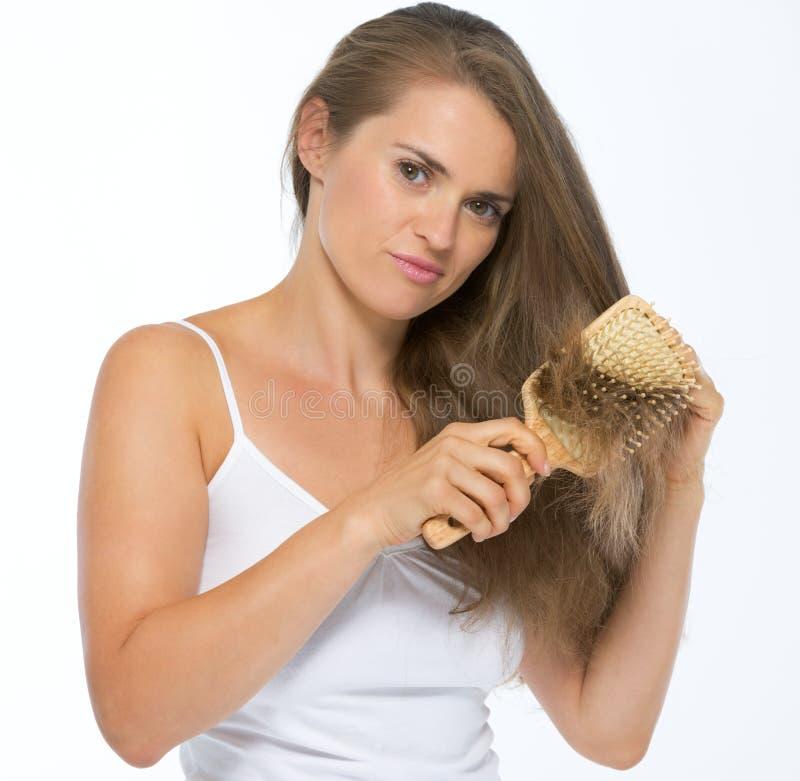 Frustrierte junge Frau, die Haar kämmt stockbilder