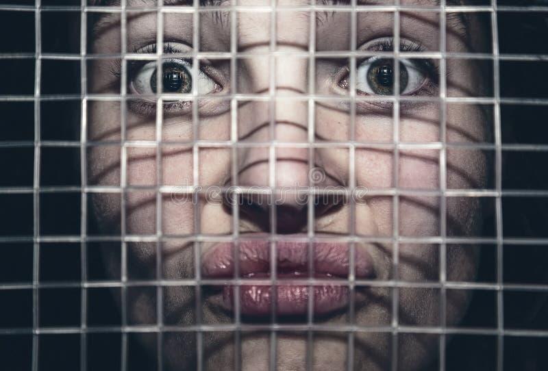 Frustrierte junge Frau hinter dem Gitter einer Tennisrakete stockfotos