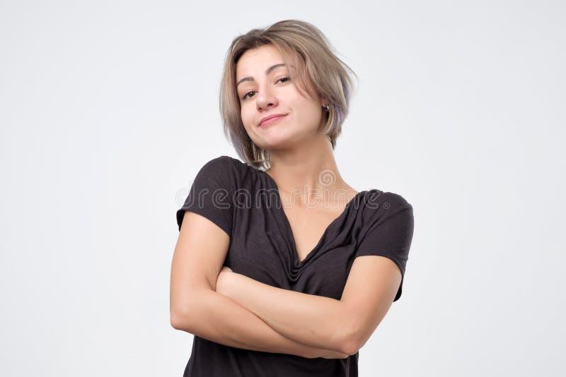 Frustrierte junge Frau mit den gekreuzten Händen steht auf Weiß stockfotos