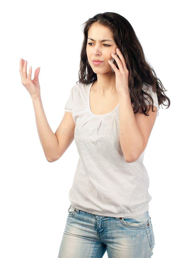 Frustrierte junge Frau am Telefon stockbilder