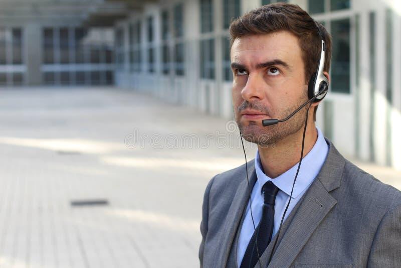 Frustrierte Kundendienstarbeitskraft, die seine Augen rollt lizenzfreies stockbild