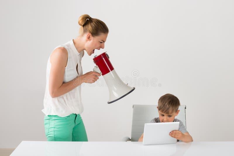 Frustrierte Mutter, die an ihrem Jungen schreit lizenzfreies stockfoto