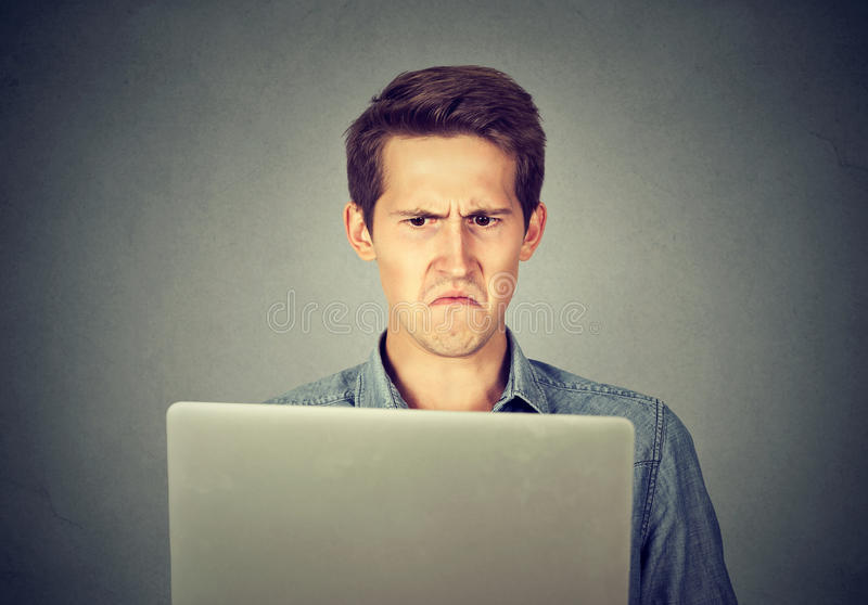 Frustrierter angewiderter Mann, der den Laptop missfallen betrachtet stockfoto