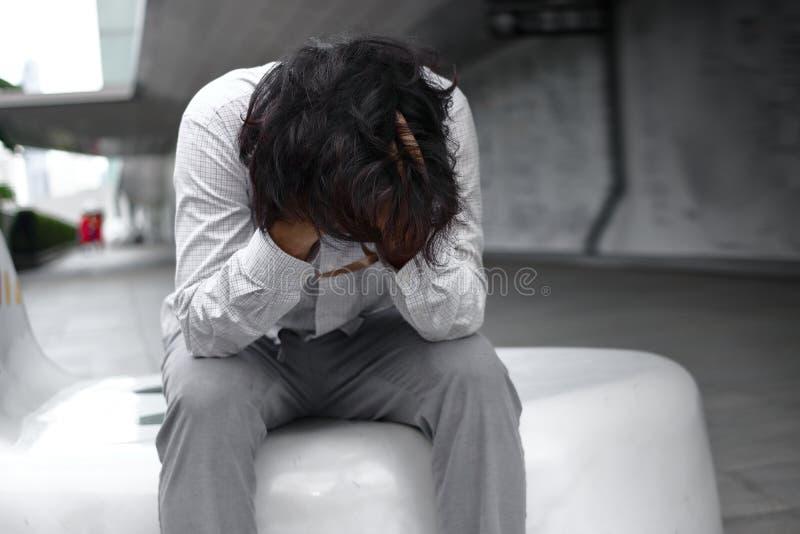 Frustrierter betonter junger asiatischer Geschäftsmann mit den Händen, die Gesicht bedecken und disappionted oder mit Job erschöp lizenzfreie stockbilder