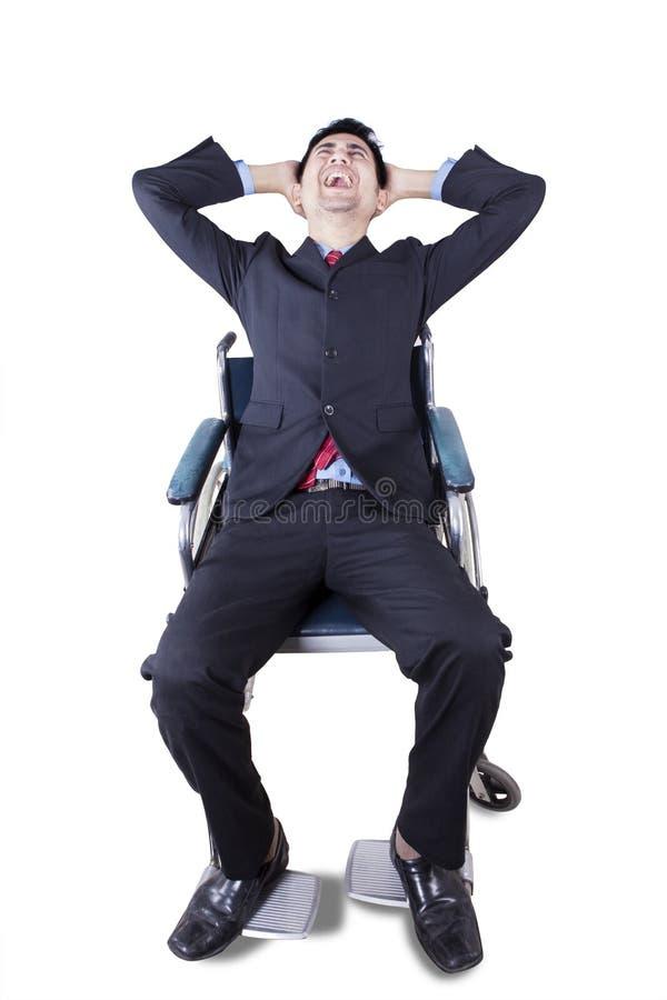 Frustrierter Geschäftsmann sitzt auf Rollstuhl lizenzfreies stockbild