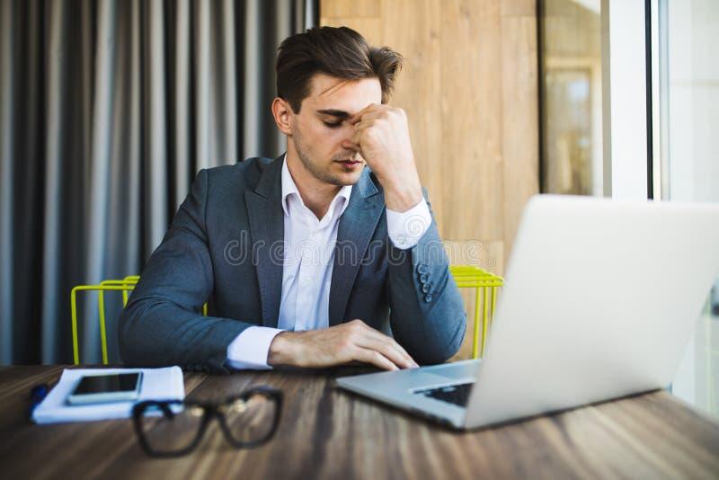 Frustrierter junger Geschäftsmann, der an Laptop-Computer im Büro arbeitet lizenzfreies stockbild