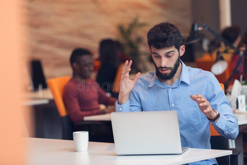 Frustrierter junger Geschäftsmann, der an Tischrechner arbeitet lizenzfreie stockfotos