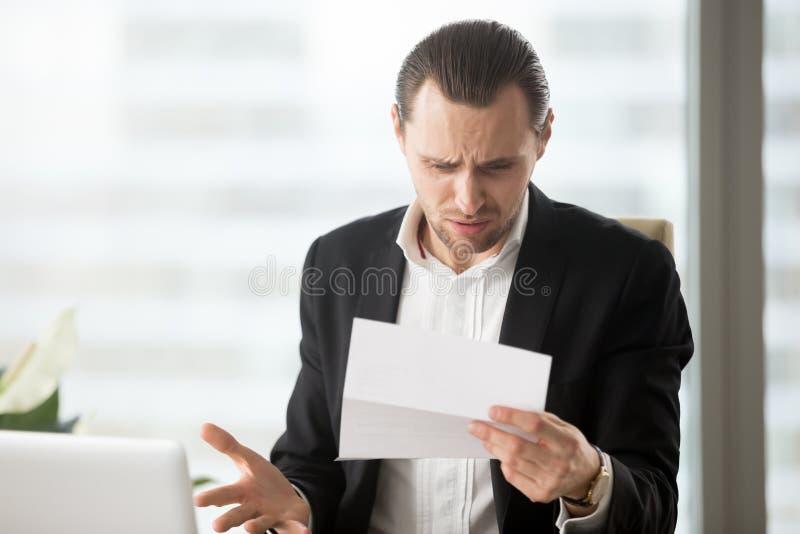 Frustrierter junger Geschäftsmann, der verwirrenden Buchstaben im offi betrachtet stockbild