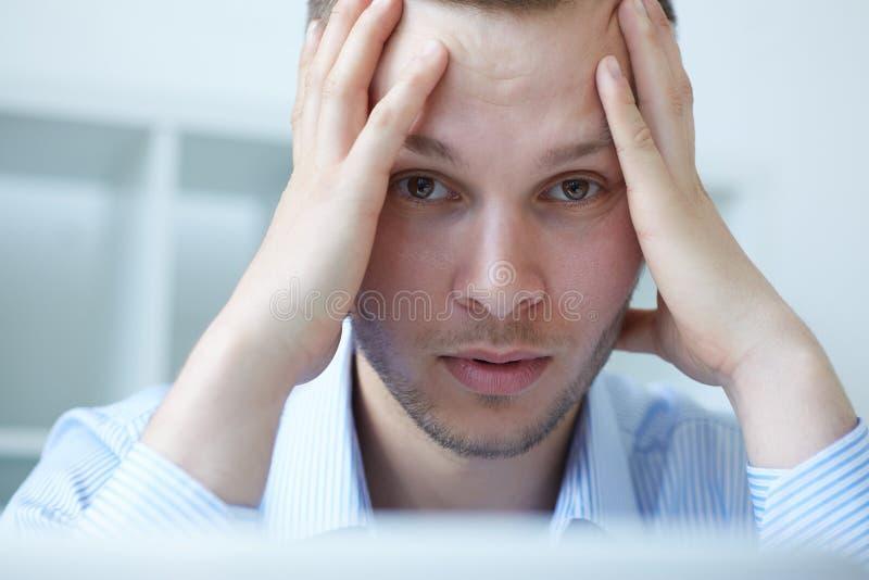 Frustrierter junger gutaussehender Mann, der beim Sitzen seinem Arbeitsplatz erschöpft betrachtet lizenzfreie stockfotos
