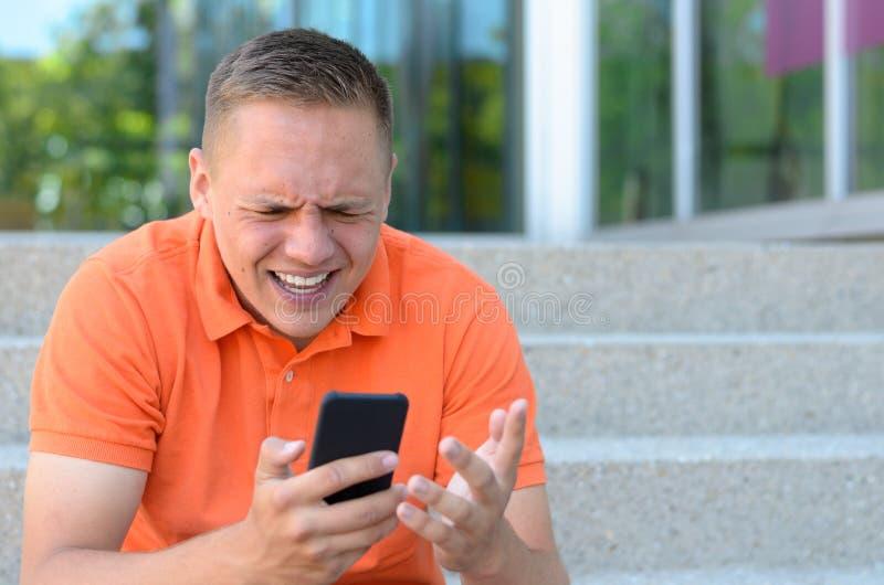 Frustrierter junger Mann, der an seinem Handy gestikuliert lizenzfreie stockfotos