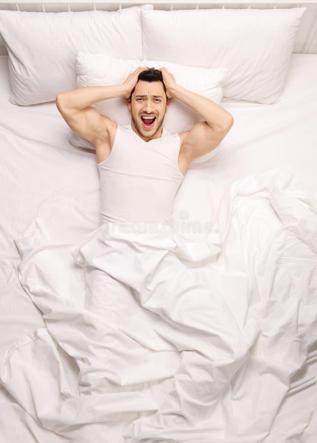 Frustrierter Kerl, der im Bett liegt lizenzfreie stockbilder