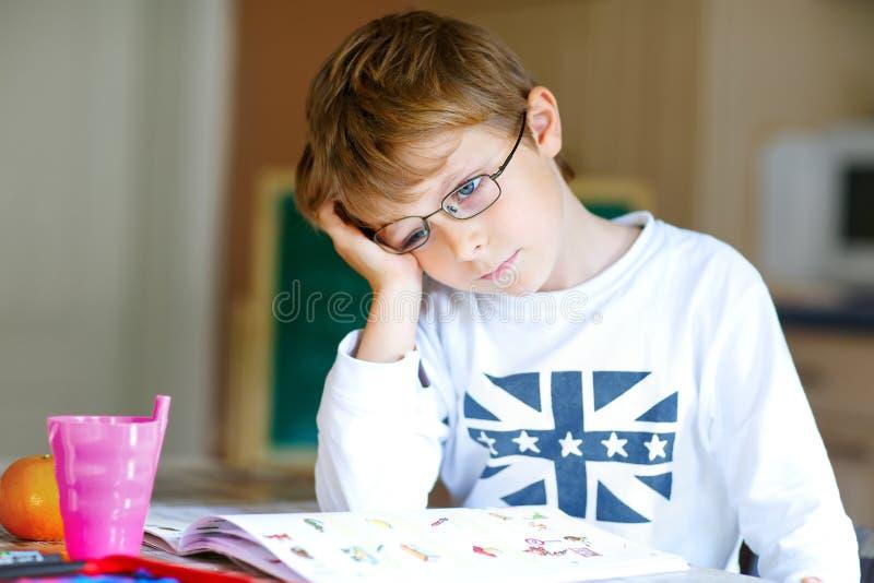 Frustrierter Kinderjunge mit den Gläsern zu Hause, die Hausarbeit machen lizenzfreie stockbilder