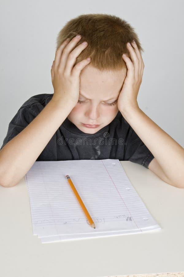 Frustrierter kleiner Junge, der homeword tut stockfotografie