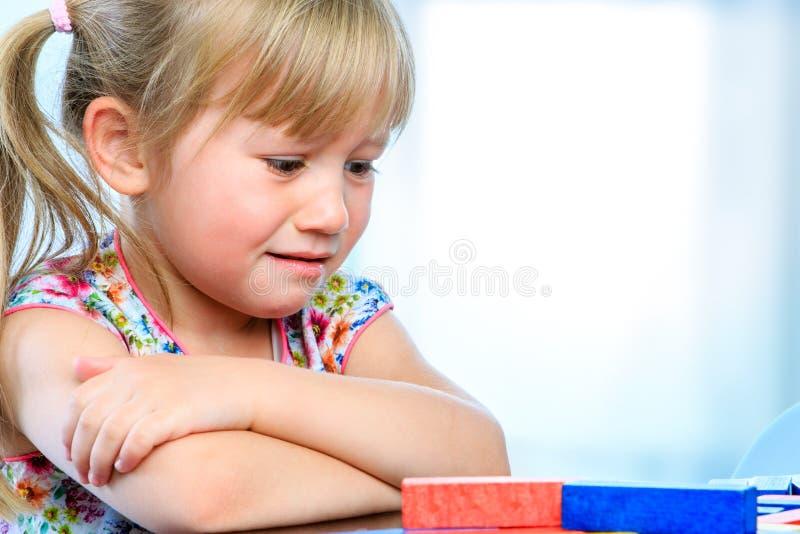 Frustrierter Knabe bei Tisch mit Spiel stockfotos