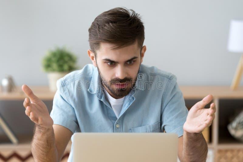 Frustrierter Mann, der den Bildschirm sitzt am Schreibtisch betrachtet lizenzfreie stockbilder