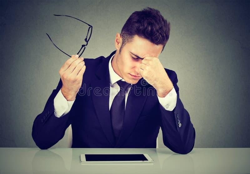 Frustrierter Mann, der erschöpftes glaubendes müdes Sitzen seinem Arbeitsplatz betrachtet und seine Gläser in der Hand trägt stockbilder