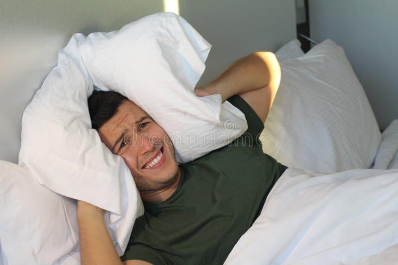 Frustrierter Mann, der seine Ohren mit Kissen bedeckt lizenzfreies stockfoto